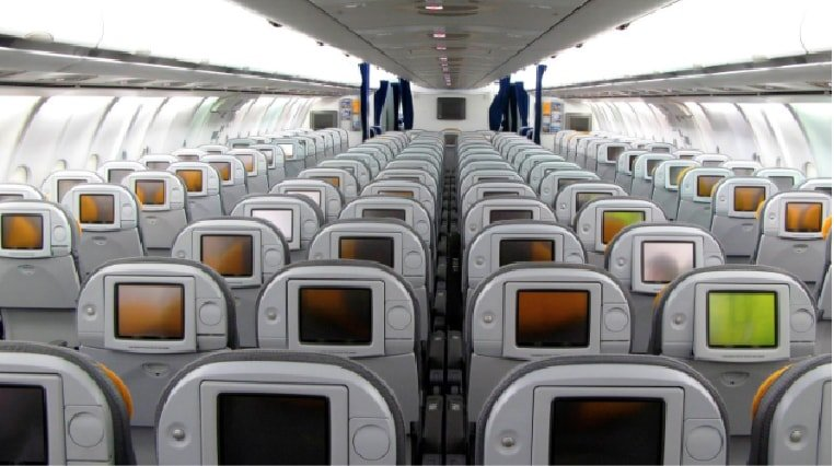 Cabin of airbus 340 with tv monitors in the backs of the seats